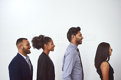 Buy stock photo Studio shot of a group of young businesspeople standing in line against a gray background