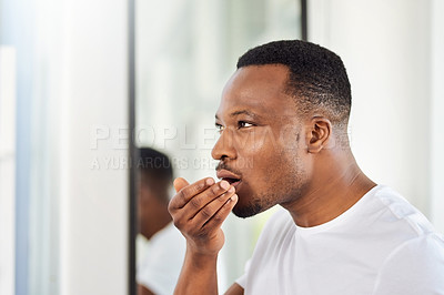 Buy stock photo Shot of a handsome young man smelling his breath during his morning grooming routine