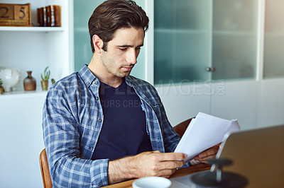 Buy stock photo Shot of a focused young man doing paperwork at home while drinking coffee