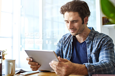 Buy stock photo Shot of a cheerful young man working on his digital tablet while being seated next to a table at home