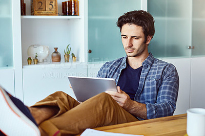 Buy stock photo Shot of a focused young man working on his digital tablet while being seated next to a table with his feet up at home
