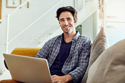 Buy stock photo Portrait of a cheerful young man working on a laptop while being seated on a couch at home