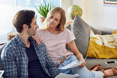 Buy stock photo Shot of a cheerful young couple working together while being seated on a couch at home