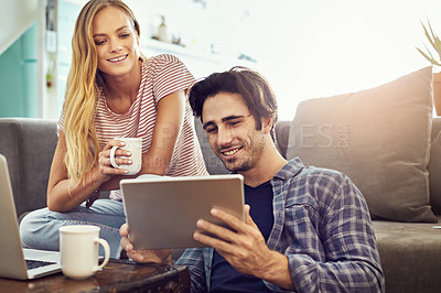 Buy stock photo Cropped shot of a young attractive couple using wireless technology at home