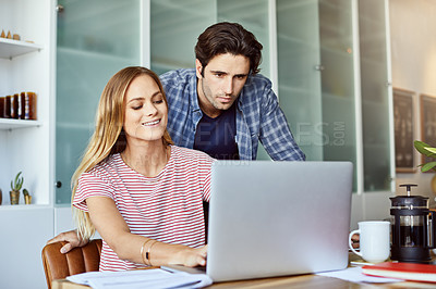 Buy stock photo Shot of a focused young couple working together on a laptop while being seated next to table at home