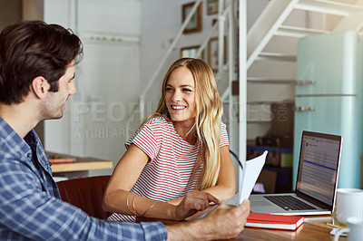 Buy stock photo Shot of a focused young couple doing paperwork together while being seated next to a table at home