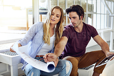 Buy stock photo Shot of a focused young couple drawing plans and choosing colors for the renovation of their house