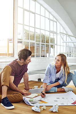 Buy stock photo Shot of a focused young couple drawing plans and choosing colors for the renovation of their house while being seated on the floor
