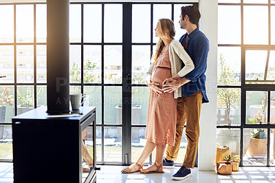 Buy stock photo Shot of a young man embracing his pregnant wife and looking out of a window at home