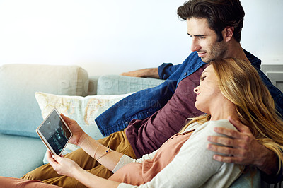 Buy stock photo Shot of a young man and his pregnant wife looking at a sonogram on a digital tablet on the sofa