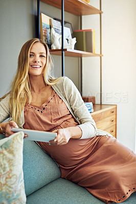 Buy stock photo Shot of a pregnant woman using a digital tablet at home