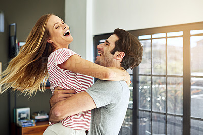 Buy stock photo Shot of a happy young man lovingly picking up his wife at home