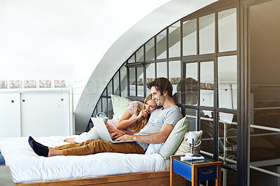 Buy stock photo Shot of a young couple using a laptop together while relaxing on the bed at home