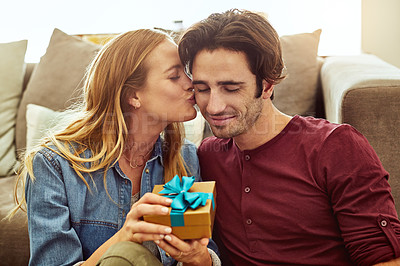 Buy stock photo Shot of a young woman giving her husband a gift at home