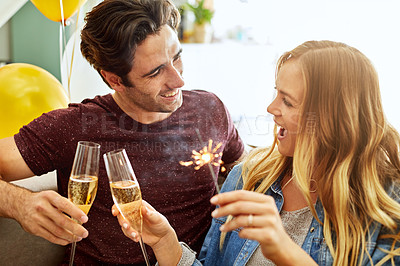 Buy stock photo Shot of a young couple toasting with champagne to celebrate at home