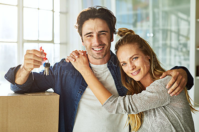Buy stock photo Shot of an affectionate young couple holding up the keys to their new home