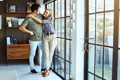 Buy stock photo Shot of a happy young couple standing next to a glass door at home