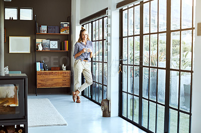 Buy stock photo Full length shot of an attractive young woman enjoying a coffee while standing by a glass door at home