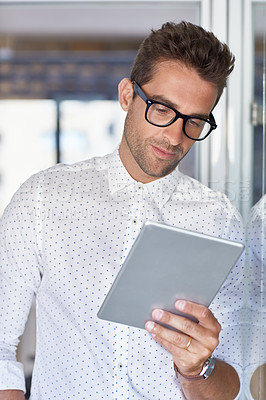 Buy stock photo Cropped shot of a young businessman using his digital tablet in his office