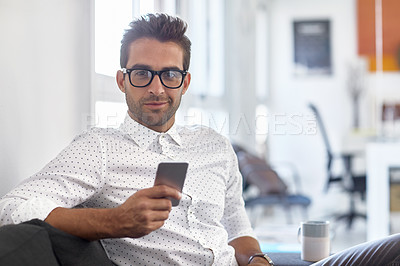 Buy stock photo Cropped shot of a young man using his cellphone in his office