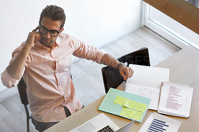 Buy stock photo Shot of a young businessman talking on his phone while sitting at his desk