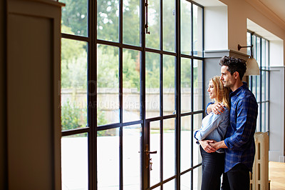 Buy stock photo Shot of a young couple looking out the window t home
