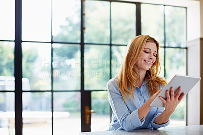 Buy stock photo Shot of a young woman using a digital tablet at home