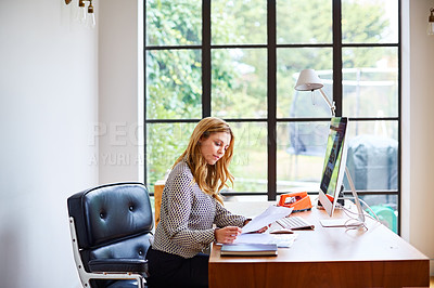 Buy stock photo Shot of a young woman going through paperwork while working from home
