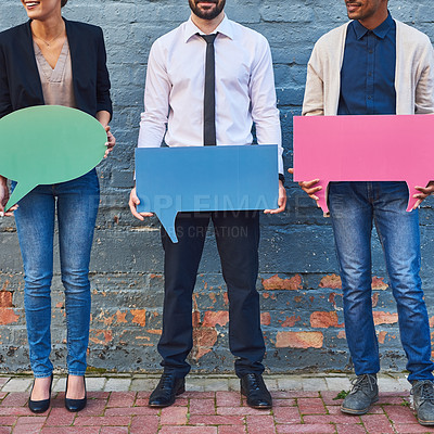 Buy stock photo Shot of a group of businesspeople holding speech bubbles against a brick wall outdoors