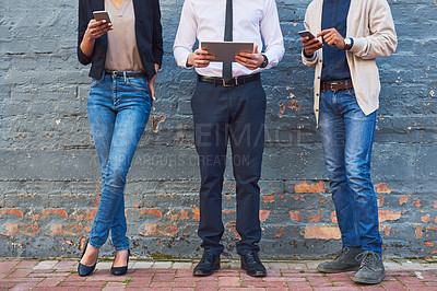 Buy stock photo Shot of a group of unrecognizable businesspeople using digital devices against a brick wall outdoors