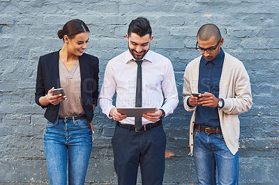 Buy stock photo Shot of a group of businesspeople using digital devices against a brick wall outdoors