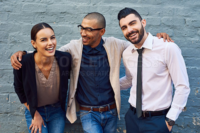 Buy stock photo Portrait of a group of businesspeople standing together against a brick wall outdoors