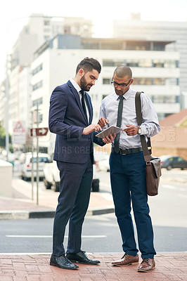 Buy stock photo Shot of two businessmen using a digital tablet together in the city