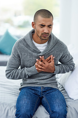 Buy stock photo Cropped shot of a young man holding his chest in pain while sitting on the bed at home