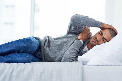 Buy stock photo Cropped shot of a young man lying on his bed while feeling unwell at home