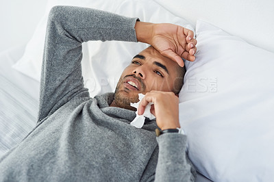 Buy stock photo High angle shot of a young man lying on his bed while feeling unwell at home