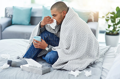 Buy stock photo Full length shot of a young man sitting on his bed while feeling unwell at home