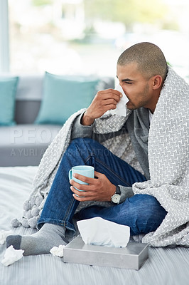 Buy stock photo Cropped shot of a young man sitting on his bed while feeling unwell at home
