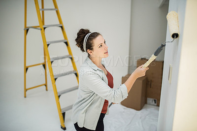 Buy stock photo Cropped shot of an attractive young woman painting the inside of her home