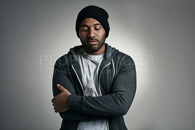Buy stock photo Cropped shot of a young homeless man in raggedy clothing posing against a grey background