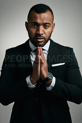 Buy stock photo Cropped portrait of a handsome young businessman praying while standing against a gray background