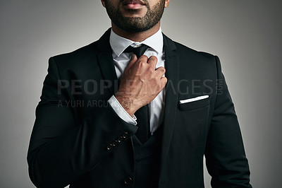 Buy stock photo Cropped shot of an unrecognizable young businessman adjusting his tie while against a gray background