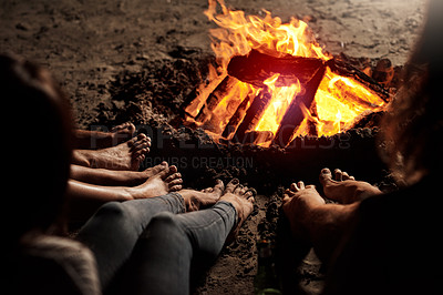 Buy stock photo Cropped shot of a group of unrecognizable friends sitting around a bonfire on the beach at night