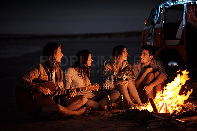 Buy stock photo Shot of a group of friends sitting around a bonfire on the beach at night