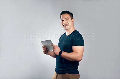 Buy stock photo Studio shot of a handsome young man posing with a tablet against a grey background