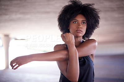 Buy stock photo Cropped shot of an attractive and athletic young woman stretching outside before her workout