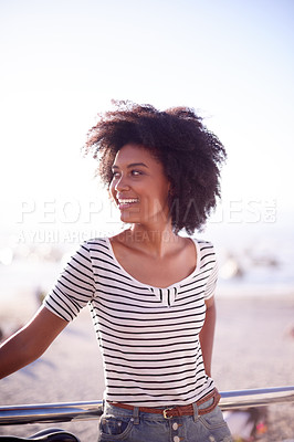 Buy stock photo Cropped shot of a young beautiful woman taking a break from riding her bicycle on the promenade at the beach