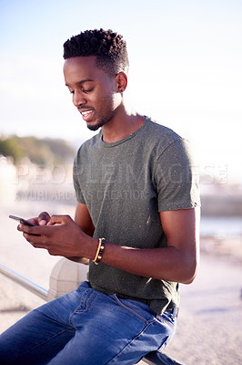 Buy stock photo Cropped shot of a young handsome man using a cellphone on the promenade at the beach