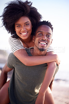 Buy stock photo Portrait of a young handsome man giving his beautiful girlfriend a piggyback ride at the beach