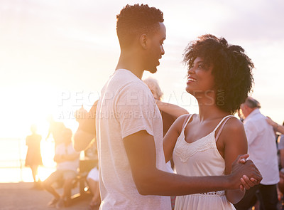 Buy stock photo Cropped shot of a young attractive couple dancing on the promenade at the beach